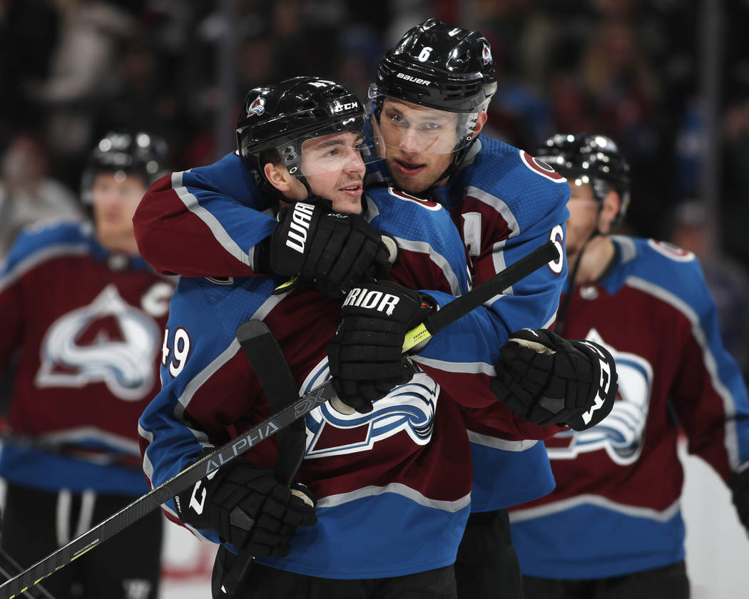 Colorado Avalanche defenseman Erik Johnson, right, hugs defenseman Samuel Girard after the third period of an NHL hockey game against the Vegas Golden Knights Monday, Feb. 18, 2019, in Denver. Col ...