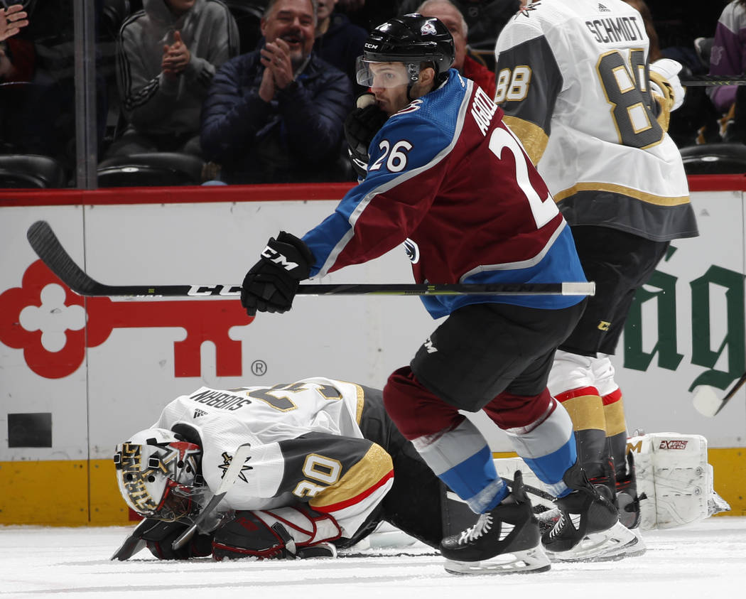 Colorado Avalanche left wing Andrew Agozzino, front, reacts after scoring a goal as Vegas Golden Knights goaltender Malcolm Subban reacts in the second period of an NHL hockey game Monday, Feb. 18 ...