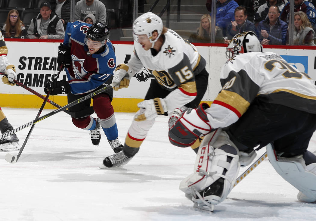 Colorado Avalanche center Tyson Jost, left, drives past Vegas Golden Knights defenseman Jon Merrill, center, to score a goal on goaltender Malcolm Subban in the first period of an NHL hockey game ...