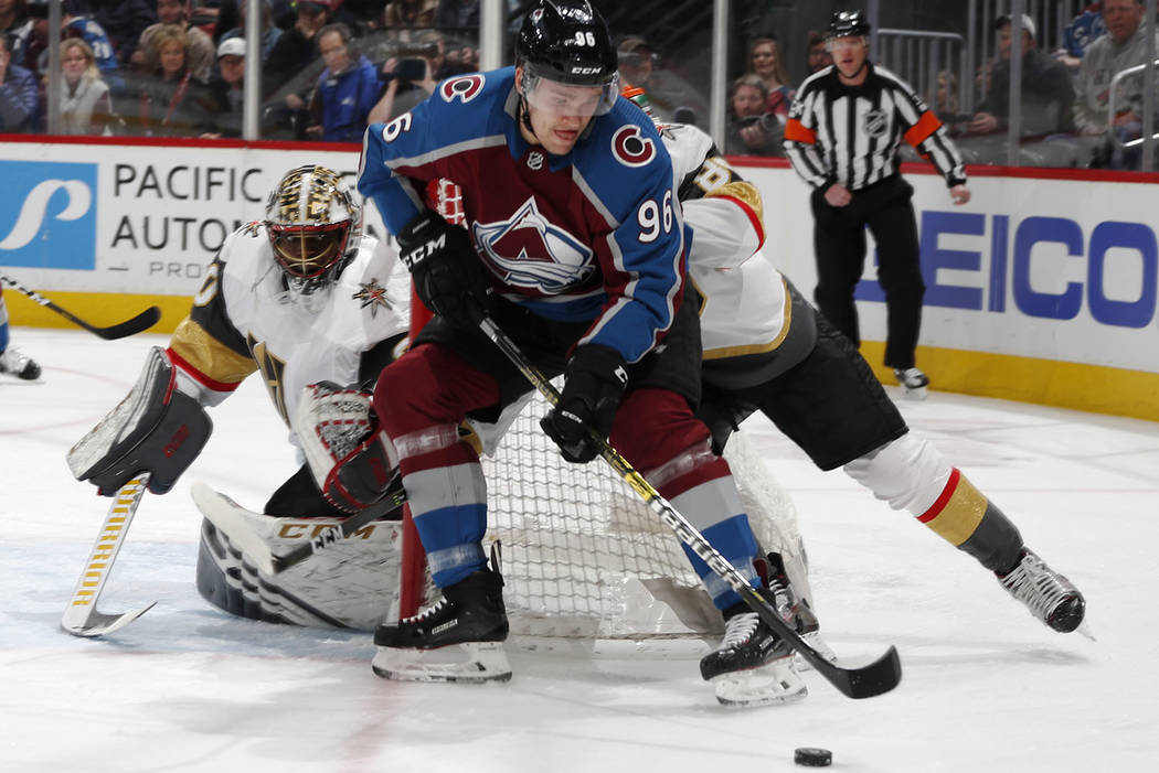 Colorado Avalanche right wing Mikko Rantanen, front, wraps around the net past Vegas Golden Knights defenseman Nate Schmidt to put a shot on goaltender Malcolm Subban in the first period of an NHL ...