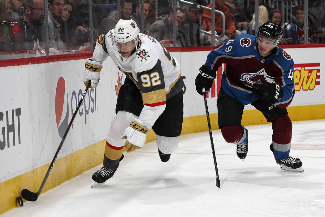 Vegas Golden Knights left wing Tomas Nosek, left, picks up the puck as Colorado Avalanche defenseman Samuel Girard pursues in the second period of an NHL hockey game Monday, Feb. 18, 2019, in Denv ...