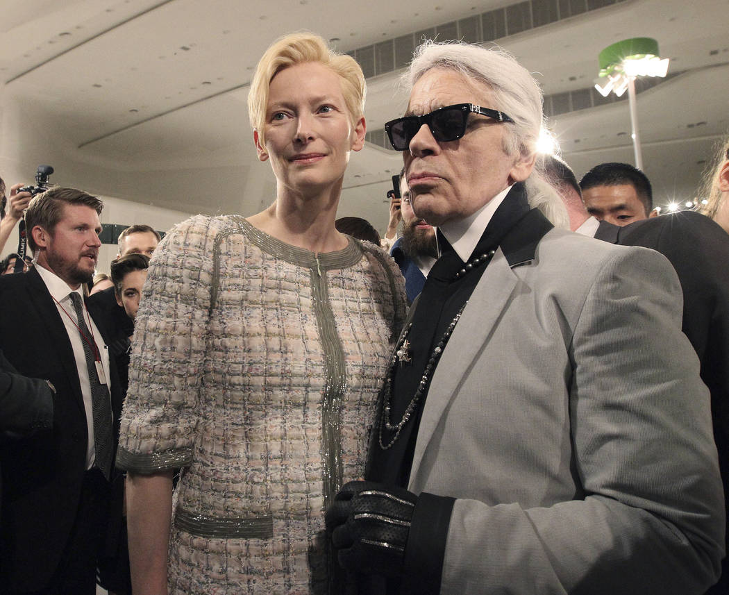 FILE - In this Monday, May 4, 2015 file photo, Karl Lagerfeld, right, poses with British actress Tilda Swinton after the presentation of his 2015-2016 Chanel cruise collection at the Dongdaemun De ...