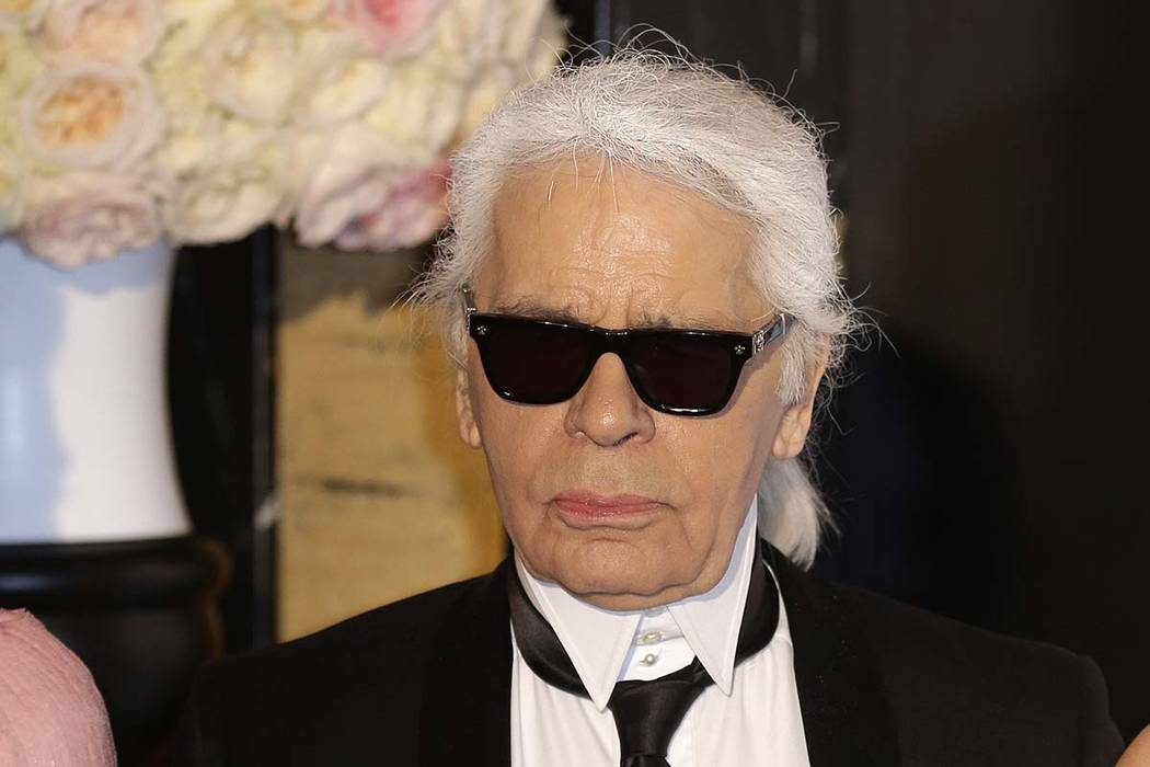 In this Saturday, March 28, 2015 file photo, Karl Lagerfeld poses for photographers as he arrives at the Rose Ball in Monaco. Chanel's iconic couturier, whose accomplished designs as well as tra ...