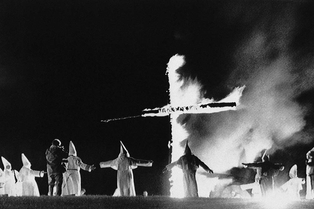 In this Sept. 27, 1987, file photo, the Invisible Empire, Ku Klux Klan members wearing traditional robes form a circle around a burning cross in Rumford, Maine. The pubisher of an Alabama weekly n ...