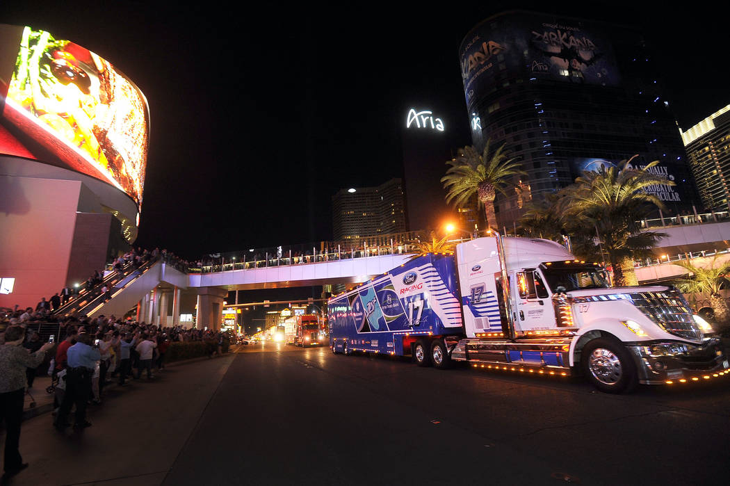 Fans watch hauler trucks during their annual parade up the Las Vegas Strip to kick off NASCAR festivities. (David Becker/Las Vegas Review-Journal)