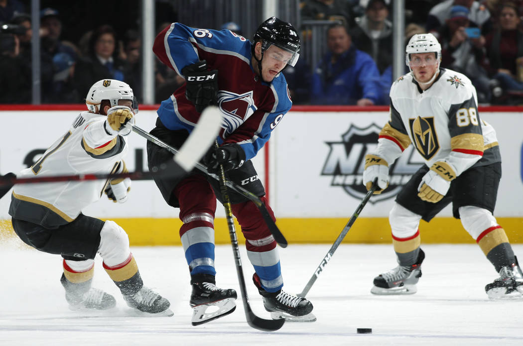 Vegas Golden Knights center Cody Eakin, left, uses his stick to slow down Colorado Avalanche right wing Mikko Rantanen, center, as Vegas defenseman Nate Schmidt follows the play in the second peri ...