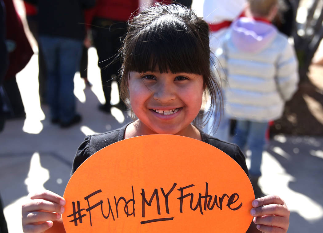 Lucy Garcia, 7, a student at Sandy Searles Miller Academy, shows off her sign as she demonstrates her support for the ''Red for Ed'' movement outside of the Grant Sawyer Building on Monday, Feb. 1 ...