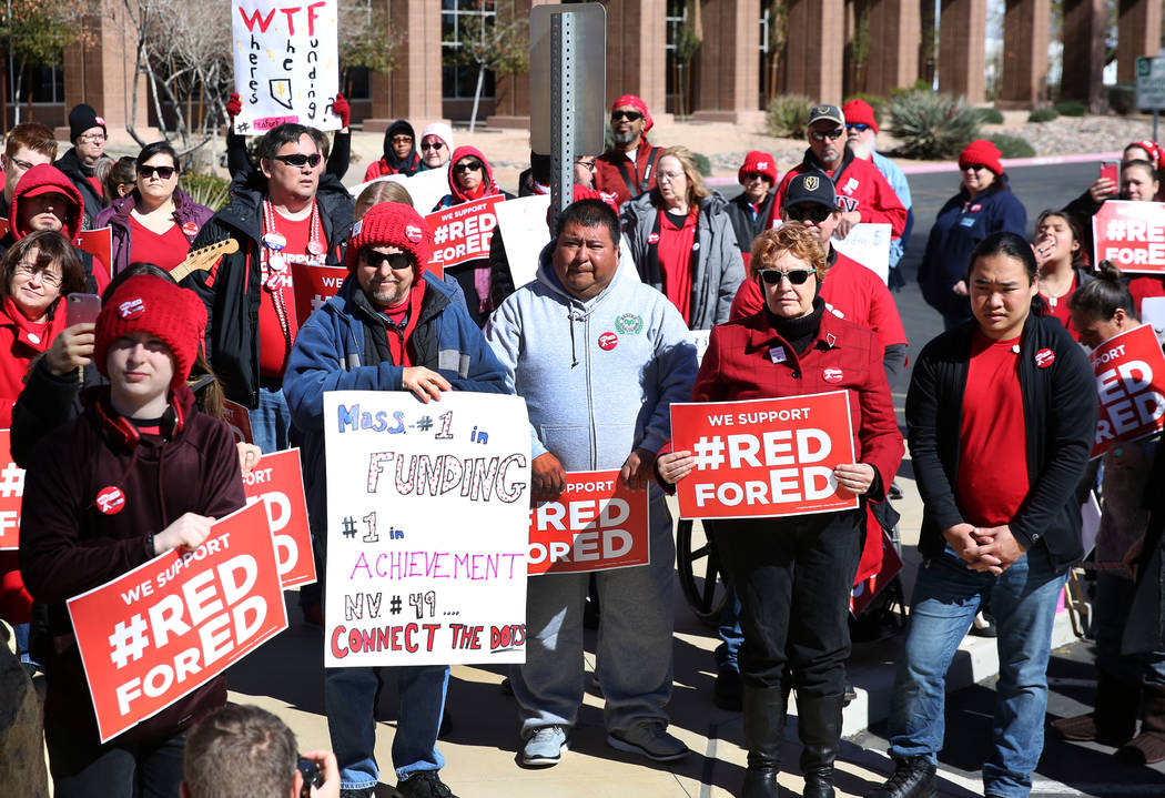 Parents and educators hold signs as they demonstrate their support for the ''Red for Ed'' movement outside of the Grant Sawyer Building on Monday, Feb. 18, 2019, in Las Vegas. Educators dressed in ...