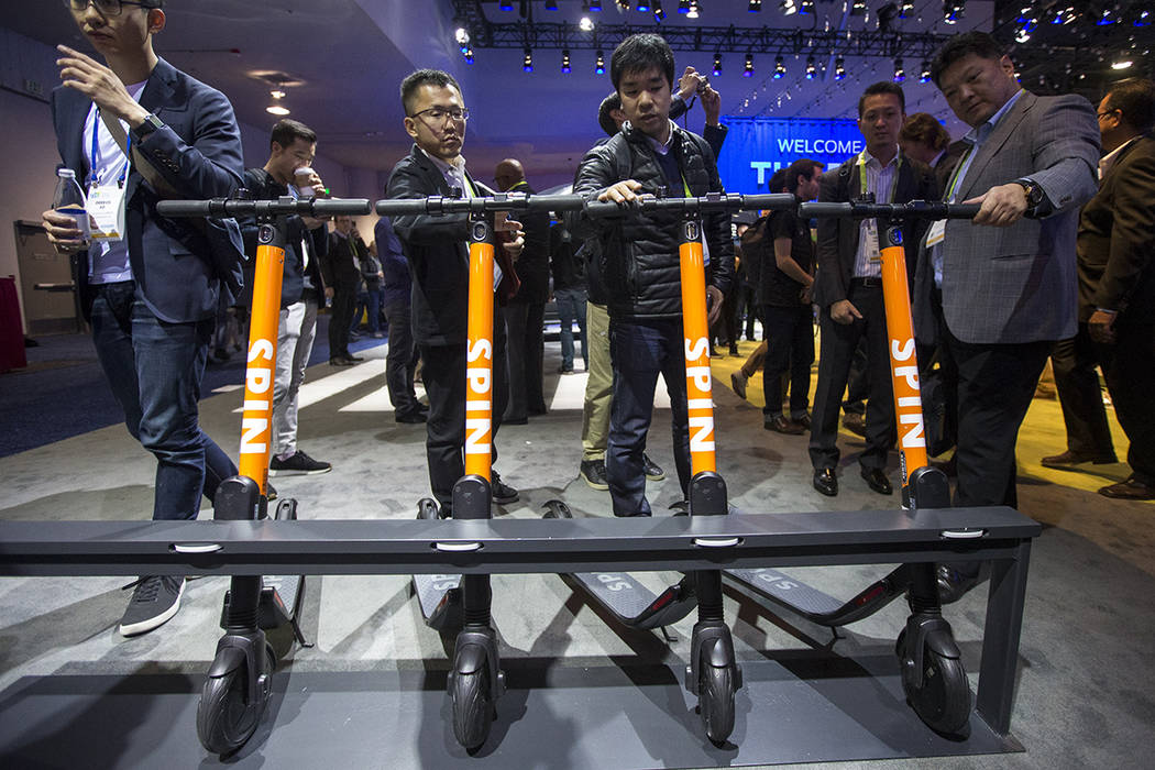 Attendees browse over the Spin electric scooters on display at the Ford Motor Co. booth on day one of CES at the Las Vegas Convention Center in Las Vegas on Tuesday, Jan. 8, 2019. Richard Brian La ...