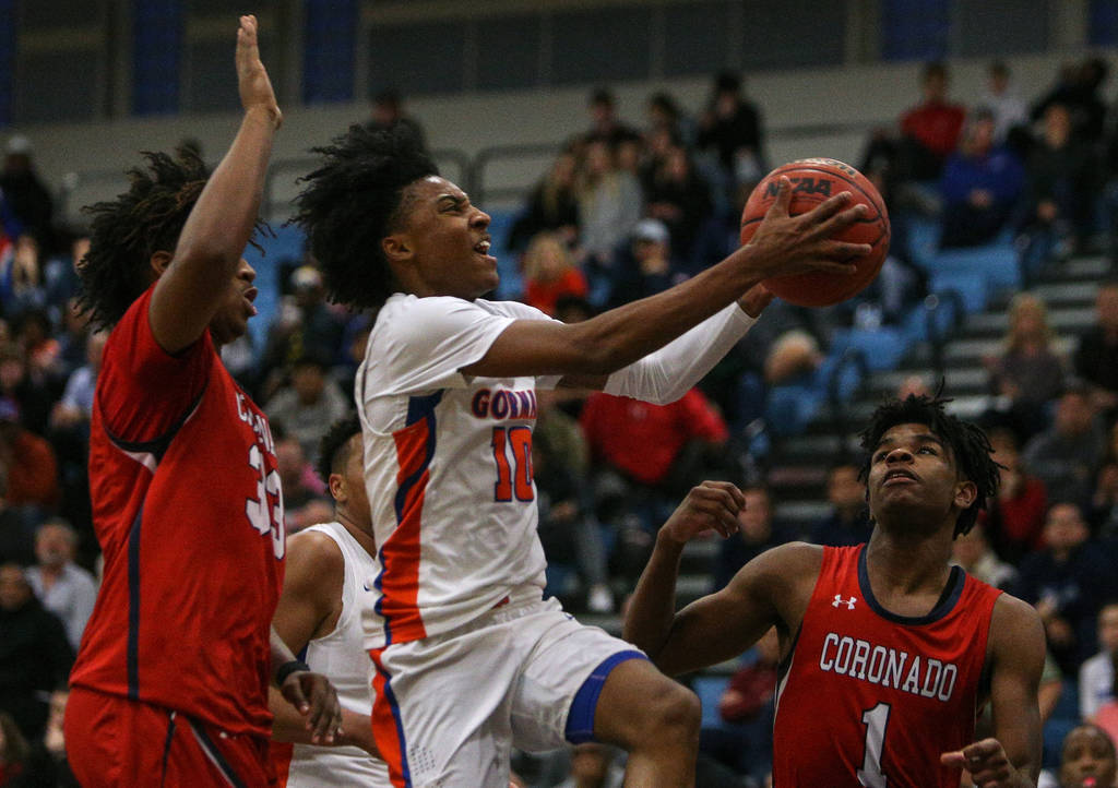 Bishop Gorman's Zaon Collins (10) jumps up to take a shot while being guarded by Coronado's Jhaylon Martinez (33) as Jaden Hardy (1) watches during the Desert Region boys semifinal game at Foothil ...