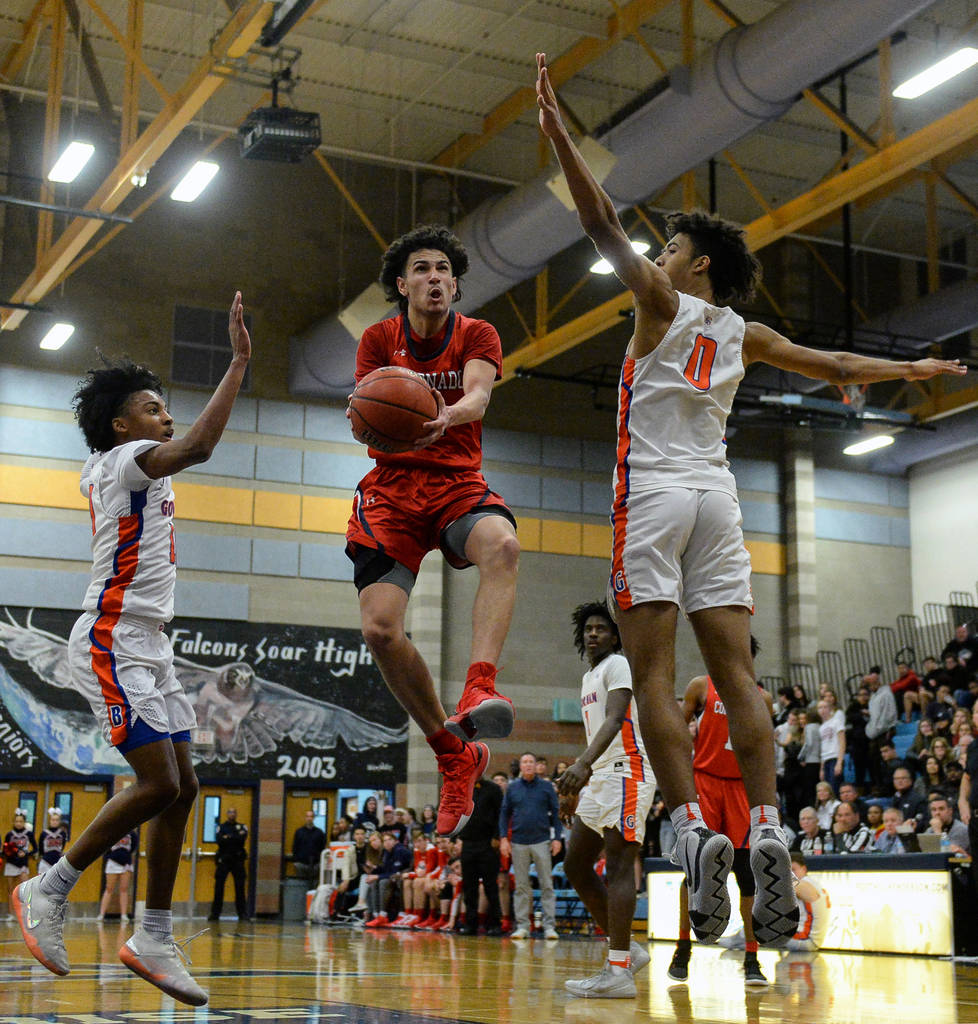 Coronado's Richard Isaacs (2) jumps up to take a shot while being guarded by Bishop Gorman's Zaon Collins (10), left, and Isaiah Cottrell (0) during the Desert Region boys semifinal game at Foothi ...