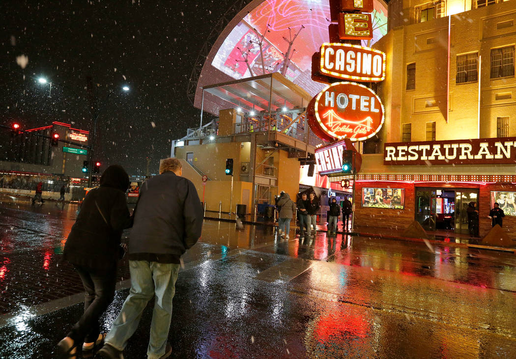Pedestrians walk as snow falls in downtown Las Vegas, Wednesday, Feb. 20, 2019. (Chitose Suzuki / Las Vegas Review-Journal) @chitosephoto