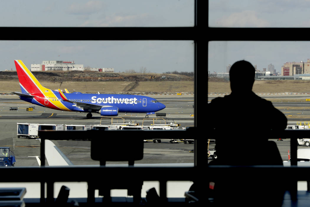 In this Jan. 25, 2019, file photo a Southwest Airlines jet moves on the runway as a person eats at a terminal restaurant at LaGuardia Airport in New York. (AP Photo/Julio Cortez, File)