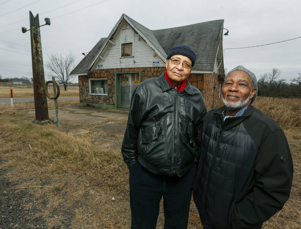 FILE - In this Dec. 3, 2018, file photo, Rev. Allen Threatt III, left, and his cousin Edward Threatt stand outside the historic Threatt Filling Station on U.S. 66 in Luther, Okla. The early gas st ...