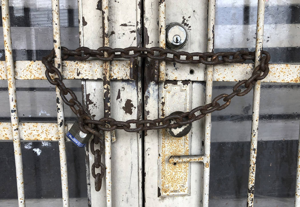 """This Feb. 12, 2019 photo, shows a lock and chain that secures the door of the old Ben Moore Hotel, once mentioned in the """"Green Book"""" for black travelers, in Montgomery, Ala. The Oscar-n ..."""