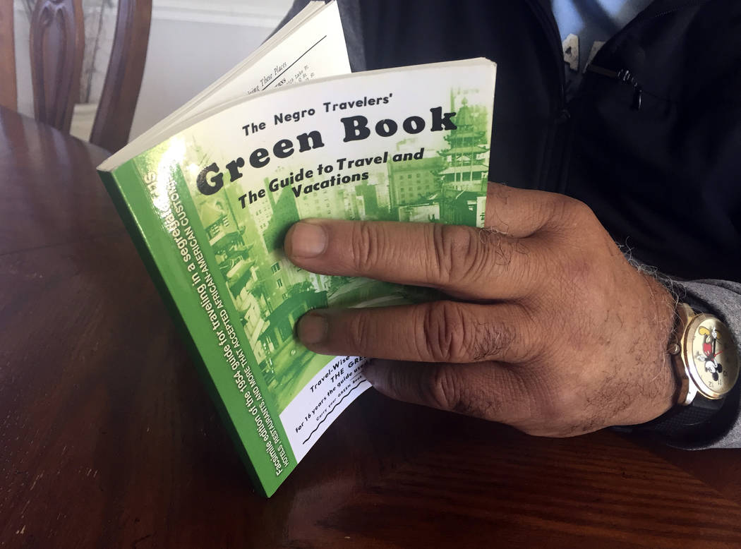 """In this Jan. 31, 2019 photo, Charles Becknell, Sr., 77, holds a copy of 1954 the edition of """"The Negro Motorist Green Book"""" at his home in Rio Rancho, N.M. The Oscar-nominated interracia ..."""