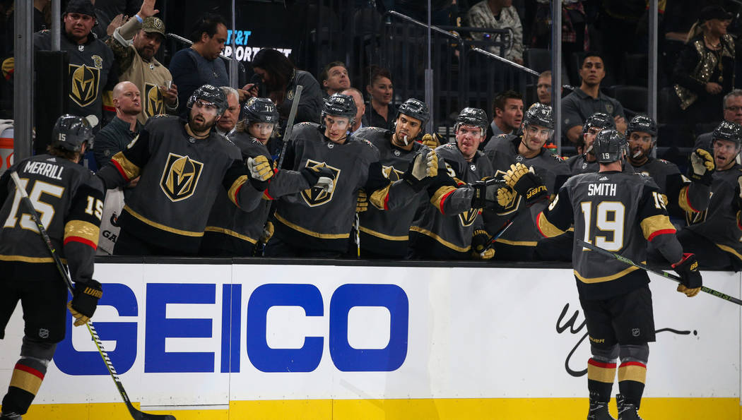 The Vegas Golden Knights high fives Vegas Golden Knights right wing Reilly Smith (19) after scoring a goal against the Boston Bruins during the first period of an NHL hockey game at T-Mobile Arena ...