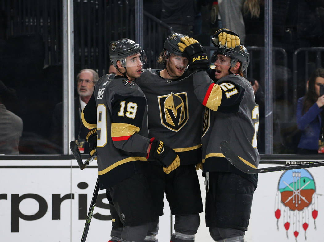 Vegas Golden Knights right wing Reilly Smith (19) celebrates his goal against the Boston Bruins with Vegas Golden Knights defenseman Jon Merrill (15) and Vegas Golden Knights center Cody Eakin (21 ...
