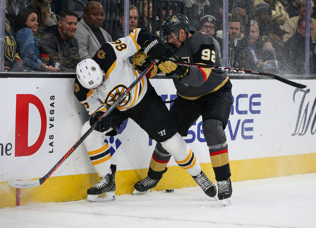 Boston Bruins defenseman Kevan Miller (86) and Vegas Golden Knights left wing Tomas Nosek (92) fight for the puck during the first period of an NHL hockey game at T-Mobile Arena in Las Vegas, Wedn ...