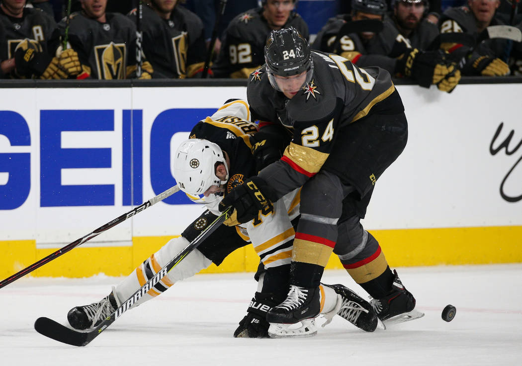 Boston Bruins left wing Jake DeBrusk (74) and Vegas Golden Knights center Oscar Lindberg (24) fight for the puck during the first period of an NHL hockey game at T-Mobile Arena in Las Vegas, Wedne ...