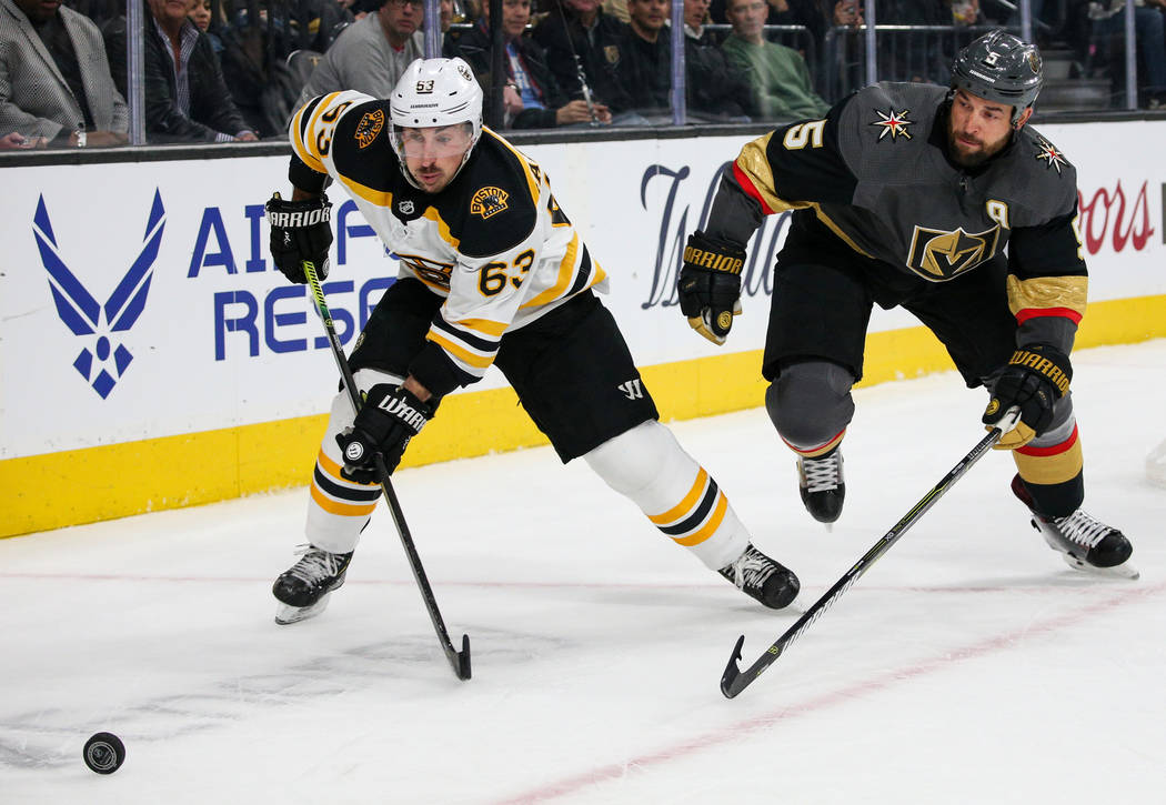 Boston Bruins left wing Brad Marchand (63) skates towards the puck as Vegas Golden Knights defenseman Deryk Engelland (5) trails behind during the second period of an NHL hockey game at T-Mobile A ...