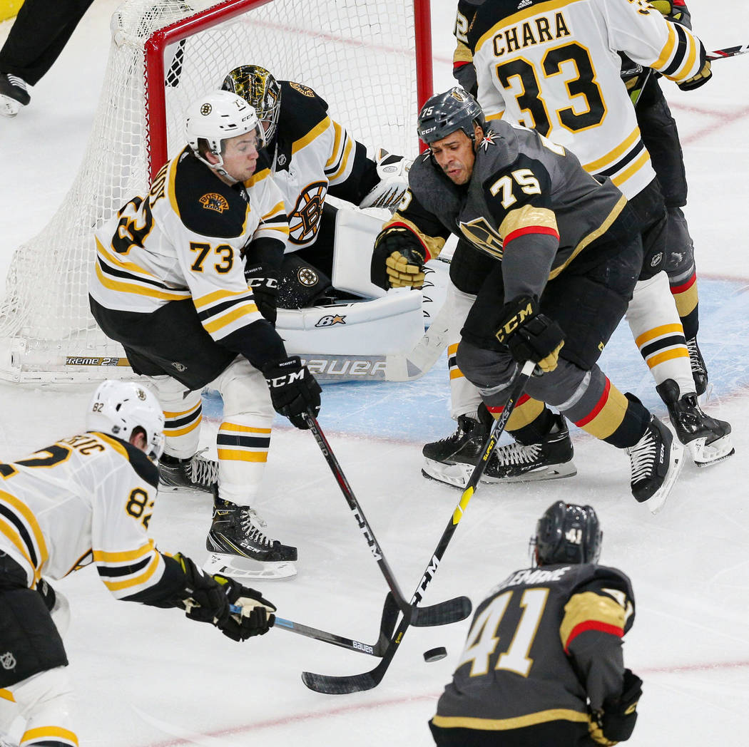 Boston Bruins center Trent Frederic (82), Boston Bruins defenseman Charlie McAvoy (73) and Vegas Golden Knights right wing Ryan Reaves (75) battle for the puck during the third period of an NHL ho ...
