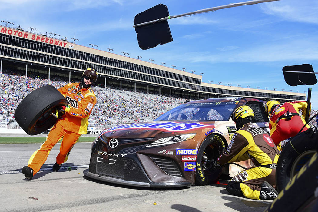 Crew members tend to Kyle Busch's car during a pit stop in a NASCAR Monster Energy NASCAR Cup Series auto race at Atlanta Motor Speedway, Sunday, Feb. 24, 2019, in Hampton, Ga. (AP Photo/Scott Cun ...