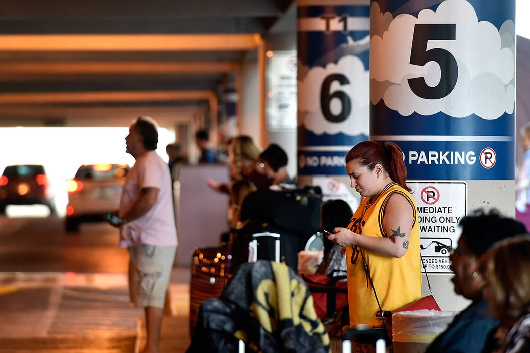 Genevieve Kocak of Las Vegas checks her mobile device as she waits for her ride in the passenger pick-up area at McCarran International Airport Monday, March 14, 2016, in Las Vegas. (David Becker ...