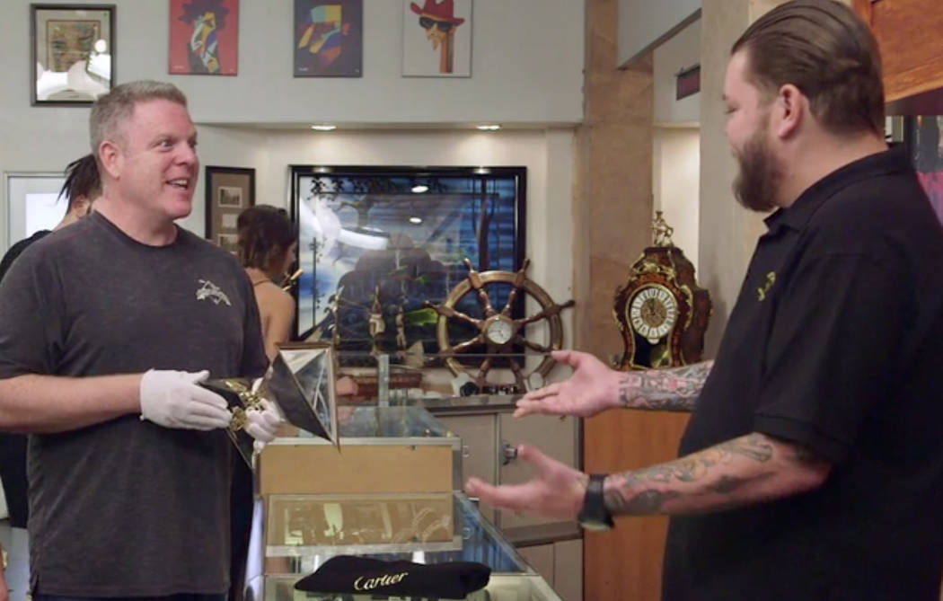 """Dan Wulkan, owner of Memory Lane Inc., left, talks to Corey Harrison about the trophy presented to Triple Crown winner Affirmed's trainer, Laz Barrera, on """"Pawn Stars."""" (History Channel)"""