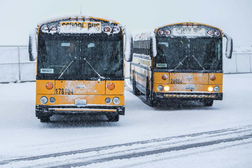 Snow-covered school buses are parked outside Centennial High School on Thursday, Feb. 21, 2019, in Las Vegas. (Benjamin Hager Review-Journal) @BenjaminHphoto