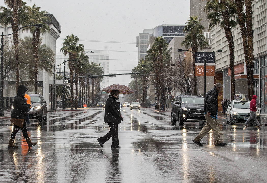 Pedestrians try to stay warm and dry in the early morning snow in Downtown Las Vegas on Thursday, Feb. 21, 2019. (Benjamin Hager Review-Journal) @BenjaminHphoto