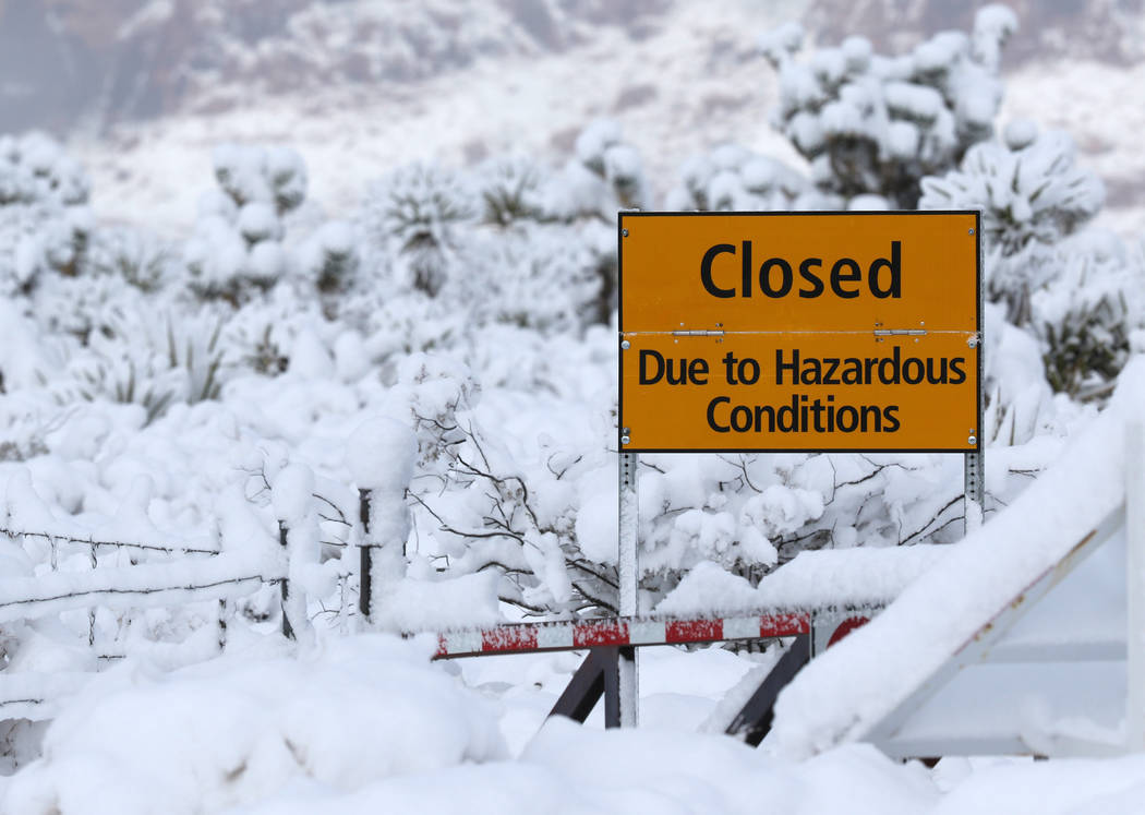 Signage is posted facing state Route 159 at the main entrance to Red Rock Canyon National Conservation Area outside Las Vegas to inform visitors that the park is closed due to snow fall in the are ...