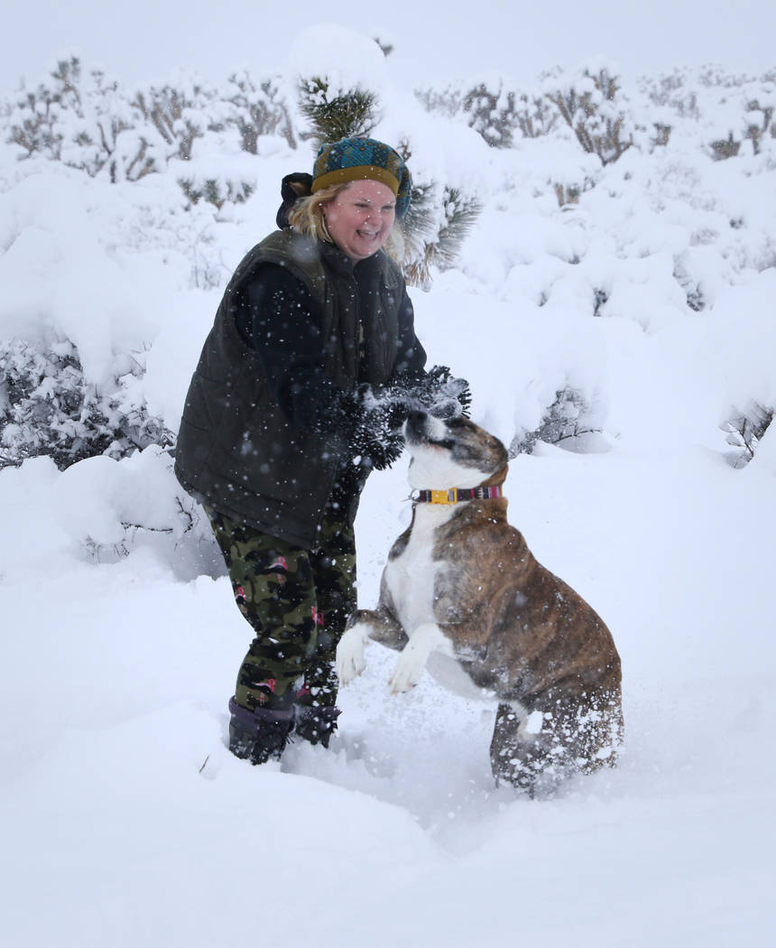Kristi Collins of Heart Butte, Montana, plays with her dog Jax as snow falls along state Route 159 near Bonnie Springs Ranch around the Red Rock Canyon National Conservation Area outside Las Vegas ...