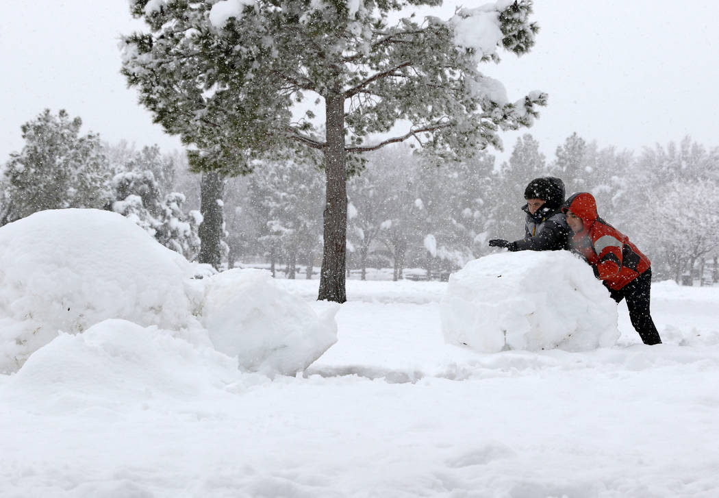 Cameron Partovi, right, and Sammy Kamyar build a snowman in South Tower Park in Summerlin as snow falls in Las Vegas, Thursday, Feb. 21, 2019. (Heidi Fang /Las Vegas Review-Journal) @HeidiFang