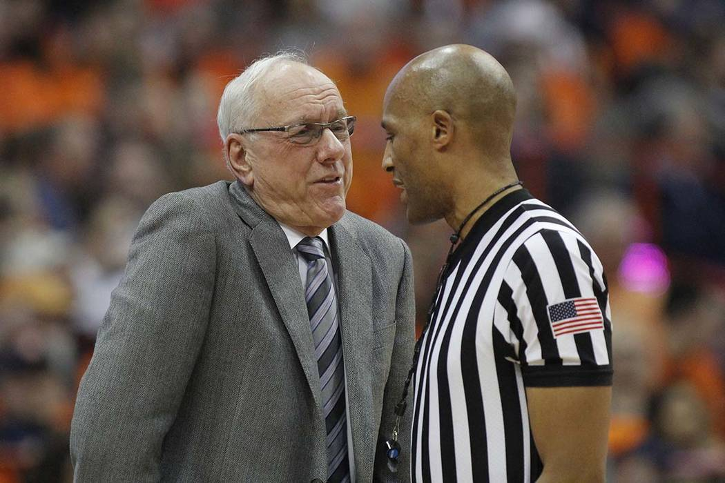 Syracuse head coach Jim Boeheim, left, talks to an official about a call during the second half of an NCAA college basketball game against Louisville in Syracuse, N.Y., Wednesday, Feb. 20, 2019. ( ...