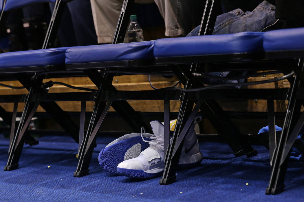 Zion Williamson's Nike shoes are seen under his chair on the Duke bench following an injury to Williamson during the opening moments of an NCAA college basketball game against North Carolina in Du ...