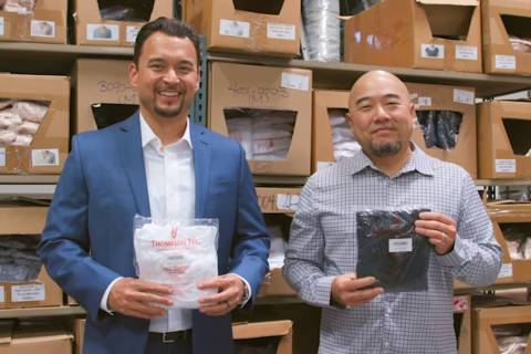 Thompson Tee co-founders Billy Thompson, left, and Randy Choi, right, hold up T-shirts inside a warehouse. (Courtesy)