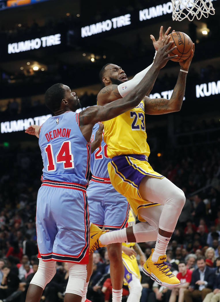 Los Angeles Lakers forward LeBron James (23) drives to the basket as Atlanta Hawks center Dewayne Dedmon (14) defends during the second half of an NBA basketball game Tuesday, Feb. 12, 2019, in At ...