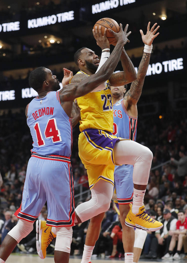 Los Angeles Lakers forward LeBron James (23) goes in for a basket as Atlanta Hawks center Dewayne Dedmon (14) defends during the second half of an NBA basketball game Tuesday, Feb. 12, 2019, in At ...
