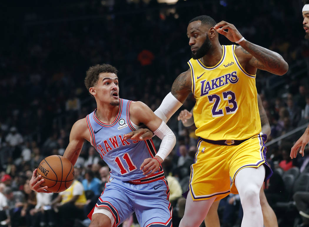 Atlanta Hawks guard Trae Young (11) is defended by Los Angeles Lakers forward LeBron James (23) during the first half of an NBA basketball game Tuesday, Feb. 12, 2019, in Atlanta. (AP Photo/John B ...