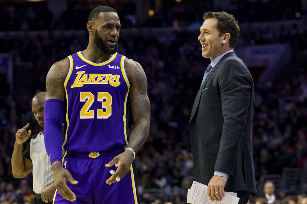 Los Angeles Lakers' head coach Luke Walton, right, talks things over with LeBron James, left, during the first half of an NBA basketball game against the Philadelphia 76ers, Sunday, Feb. 10, 2019, ...