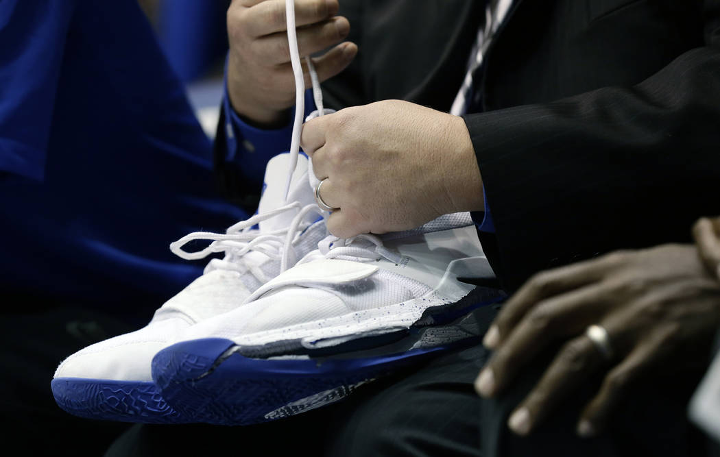 A trainer holds Duke's Zion Williamson's shoes after Williamson left the game due to an injury during the first half of an NCAA college basketball game against North Carolina in Durham, N.C., Wedn ...