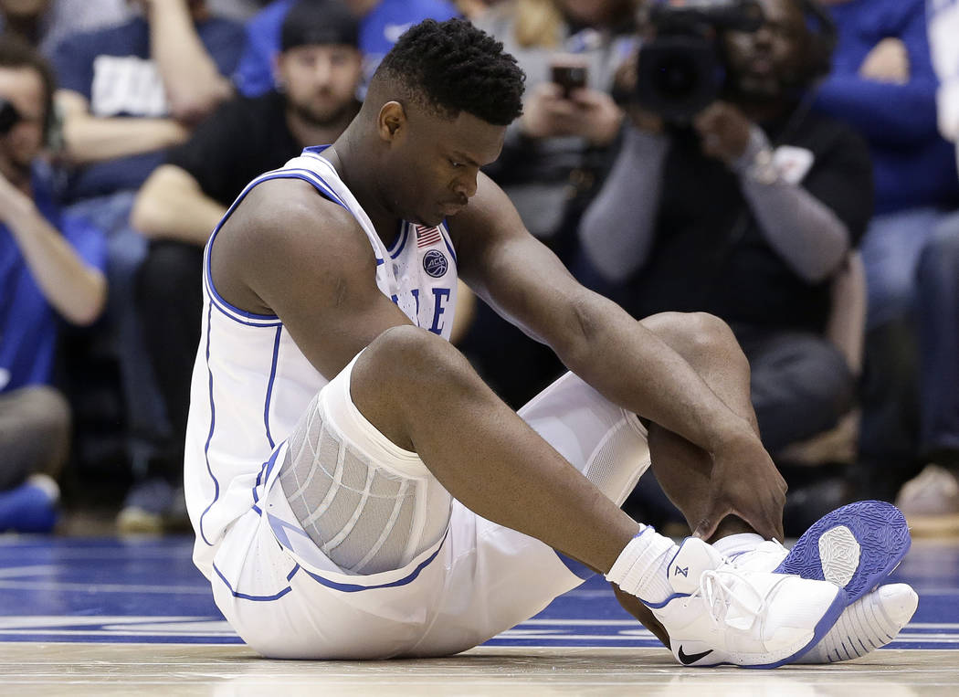 Duke's Zion Williamson sits on the floor following a injury during the first half of an NCAA college basketball game against North Carolina, in Durham, N.C., Wednesday, Feb. 20, 2019. Duke might h ...