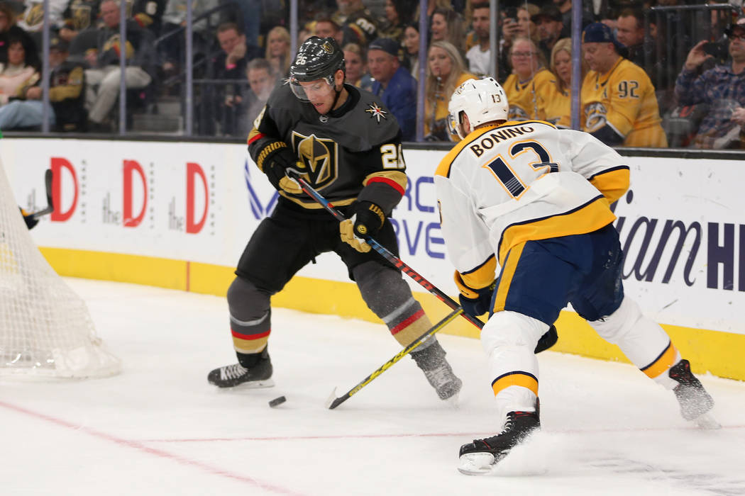 Vegas Golden Knights center Paul Stastny (26) works to make a play under pressure from Nashville Predators center Nick Bonino (13) during the first period of an NHL hockey game at T-Mobile Arena i ...