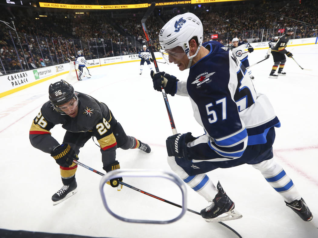 Golden Knights center Paul Stastny (26) and Winnipeg Jets defenseman Tyler Myers (57) battle for the puck during the second period of an NHL hockey game at T-Mobile Arena in Las Vegas on Friday, F ...