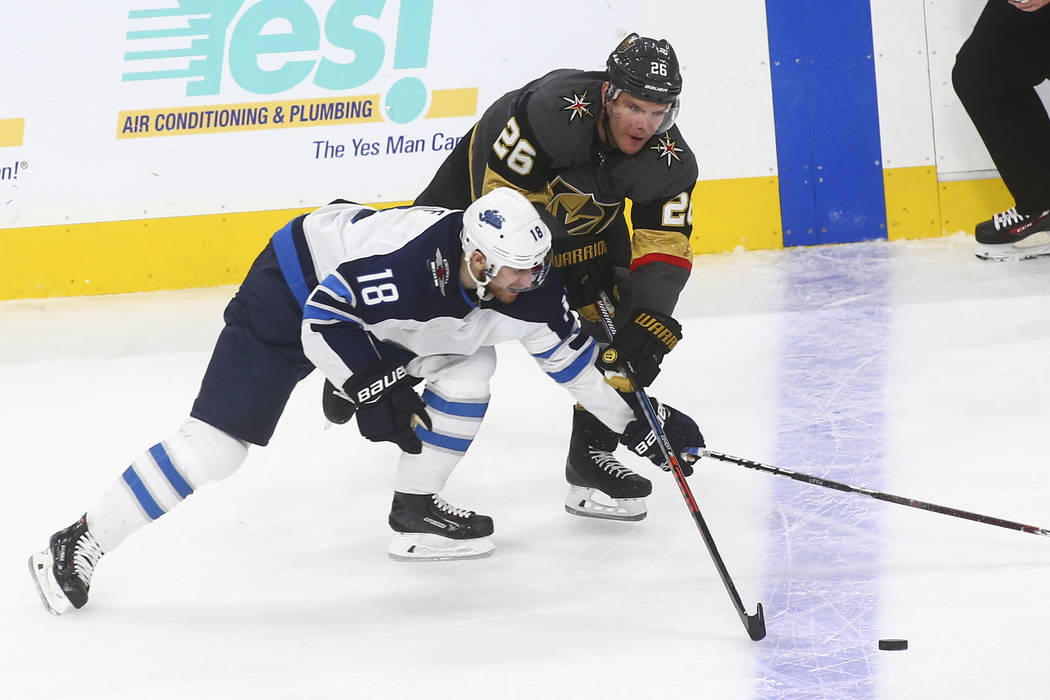 Golden Knights center Paul Stastny (26) and Winnipeg Jets center Bryan Little (18) battle for the puck during the third period of an NHL hockey game at T-Mobile Arena in Las Vegas on Friday, Feb. ...