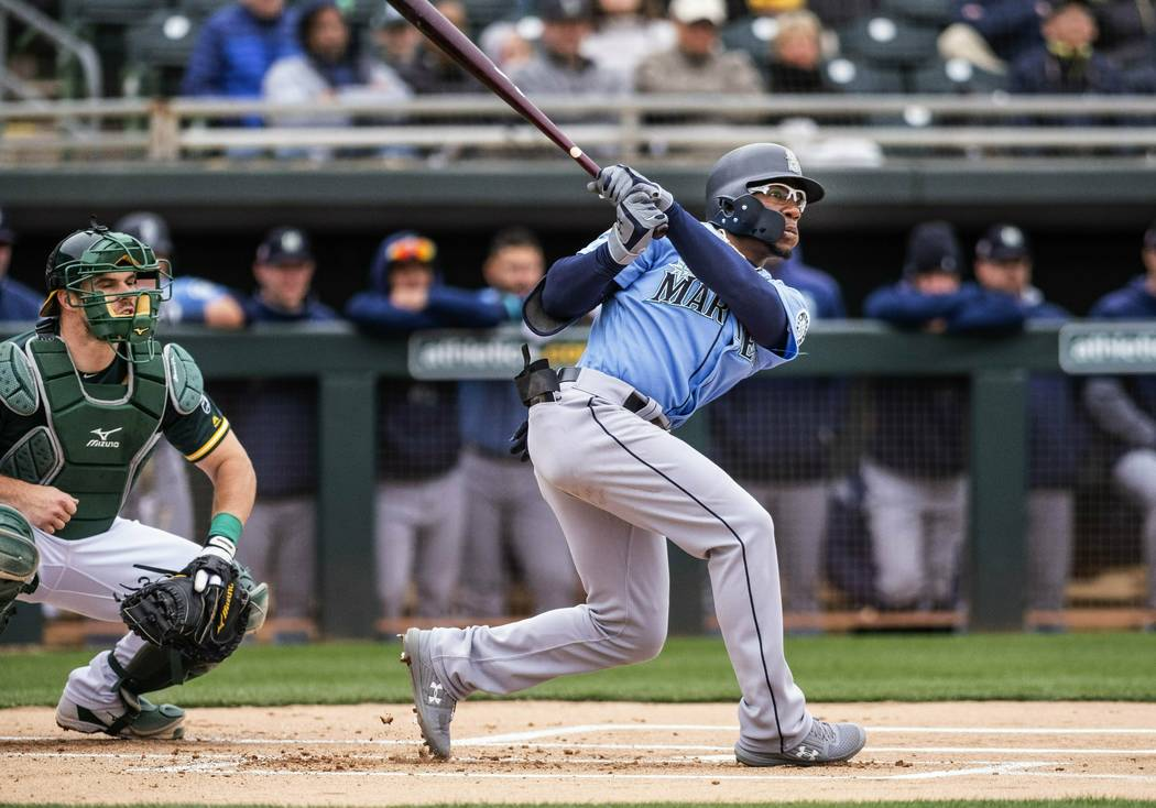 Seattle Mariners' Shed Long, right, doubles in the first inning against the Oakland Athletics during the first spring training baseball game of the season Thursday, Feb. 21, 2019, in Mesa, Ariz. ( ...