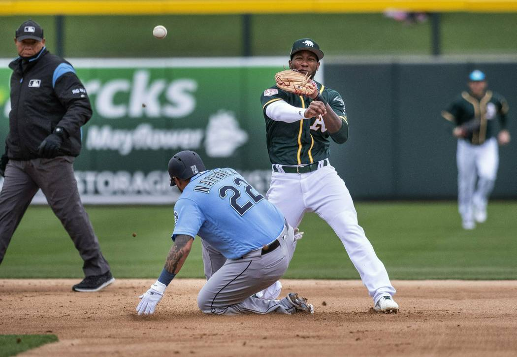 Oakland Athletics second baseman Jurdickson Profar, center right, turns a double play against Seattle Mariners' Omar Narvaez, center left, and getting Ryon Healy at first to end the top of the fir ...