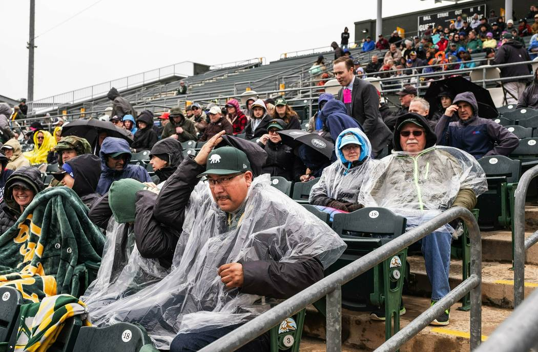 Fans at Hohokam Stadium try to cover up as rain settles in and ends up canceling a spring training baseball game between The Seattle Mariners and the Oakland Athletics after 1-1/2 innings Thursday ...