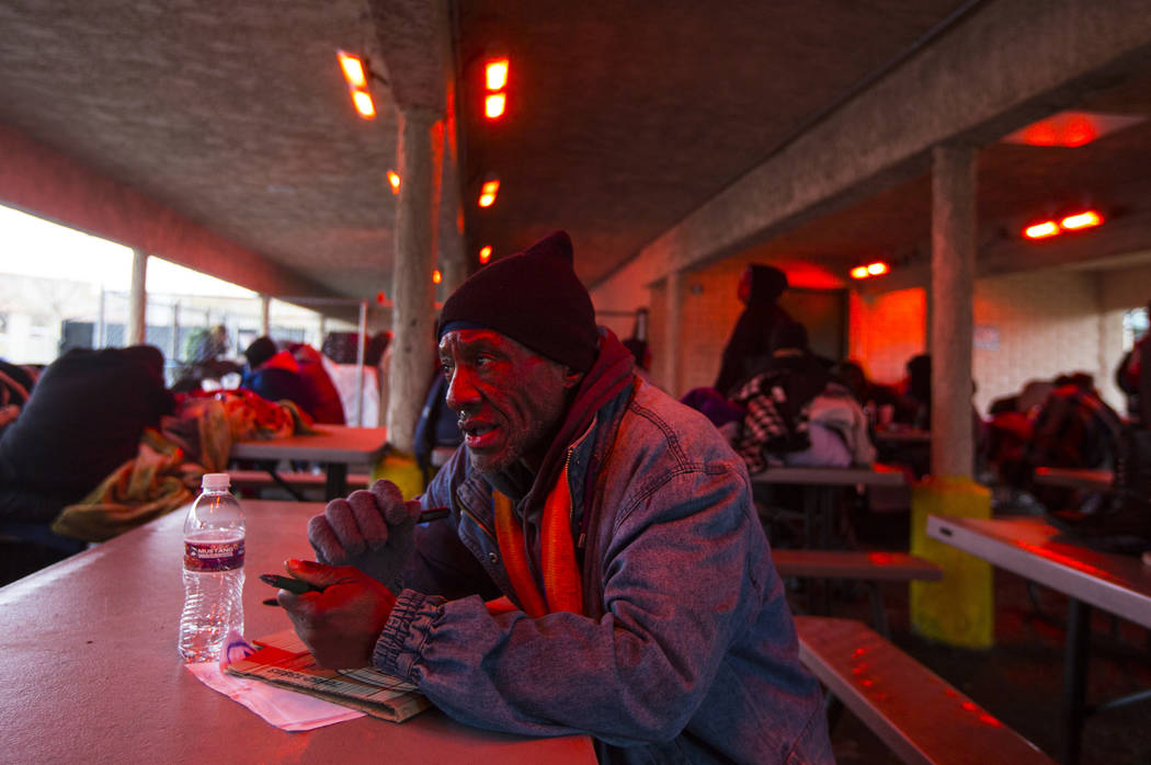 Donald Rice talks about staying warm beneath a heat lamp after a night of snowfall at the city of Las Vegas' homeless courtyard on Thursday, Feb. 21, 2019. (Chase Stevens/Las Vegas Review-Journal) ...